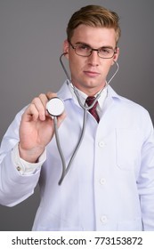 Studio shot of young handsome man doctor with blond hair against gray background