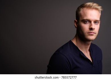 Studio shot of young handsome man with blond hair wearing blue long sleeved shirt against gray background