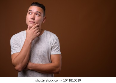 Studio shot of young handsome multi-ethnic man wearing white shirt against brown background