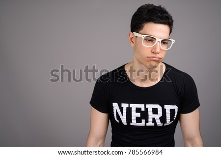 7224143ae236 Studio shot of young handsome nerd man wearing eyeglasses against gray  background