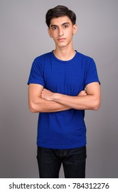 Studio shot of young handsome Persian teenage boy against gray background