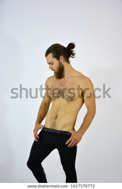 Studio shot of young handsome shirtless muscular sexy hot male model against white background.