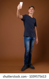 Studio shot of young handsome teenage boy wearing blue shirt against brown background