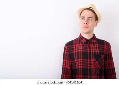 70930360 Studio shot of young handsome tourist man wearing hat and red checkered  shirt against white background