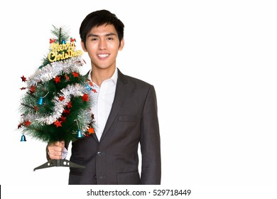 Studio shot of young happy Asian businessman holding Merry Christmas tree and smiling isolated against white background