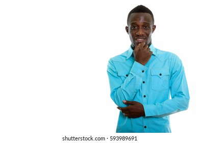 Studio shot of young happy black African man smiling while thinking