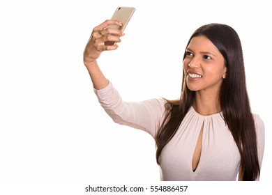 Studio shot of young happy Brazilian woman smiling while taking selfie with mobile phone isolated against white background