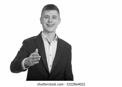Studio shot of young happy businessman smiling and giving handshake