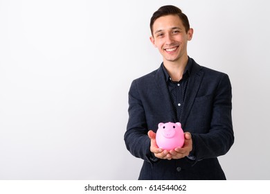 Studio shot of young happy businessman smiling while holding piggy bank against white background