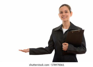 Studio shot of young happy businesswoman smiling while holding clipboard and showing something