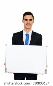 Studio shot of young happy Caucasian businessman holding empty white board isolated against white background