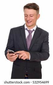 Studio shot of young happy Caucasian businessman using mobile phone isolated against white background