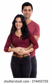 Studio shot of young happy couple smiling while hugging each other