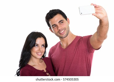 Studio shot of young happy couple smiling while taking selfie picture with mobile phone together with man holding phone