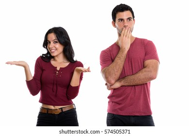Studio shot of young happy couple smiling with woman shrugging and thoughtful man looking shocked
