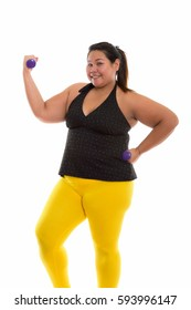 Studio shot of young happy fat Asian woman smiling and standing while exercising with dumbbells