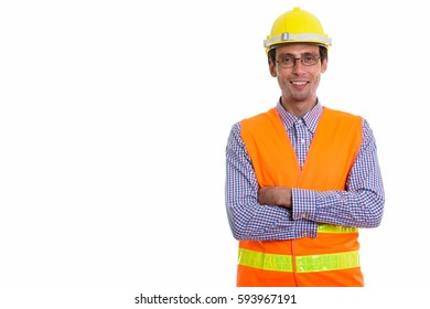 Studio shot of young happy man construction worker smiling while wearing eyeglasses with arms crossed