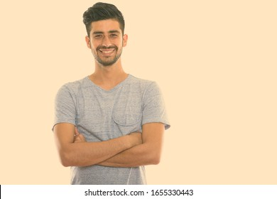 Studio shot of young happy Persian man smiling with arms crossed