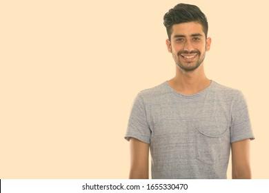 Studio shot of young happy Persian man smiling