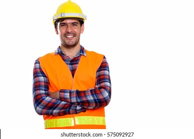 Studio shot of young happy Persian man construction worker smiling with arms crossed