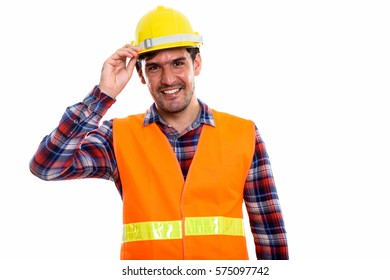 Studio shot of young happy Persian man construction worker smiling while holding helmet on head