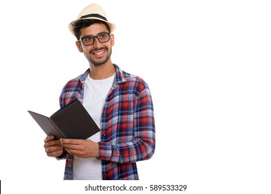 Studio shot of young happy Persian man smiling while holding book and thinking