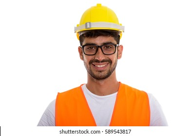 Studio shot of young happy Persian man construction worker smiling while wearing eyeglasses