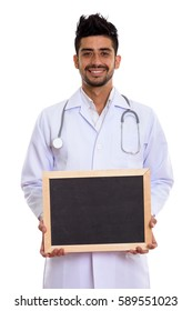 Studio shot of young happy Persian man doctor smiling while holding blank blackboard