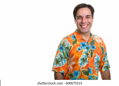 Studio shot of young happy Persian tourist man smiling while wearing Hawaiian shirt isolated against white background