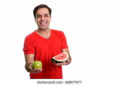 Studio shot of young happy Persian man smiling while holding slice of watermelon and green apple isolated against white background
