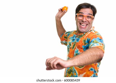 Studio shot of young happy Persian tourist man smiling and ready to throw orange fruit while wearing orange colored eyeglasses isolated against white background
