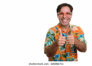 Studio shot of young happy Persian tourist man smiling while giving thumbs up with orange eyeglasses isolated against white background