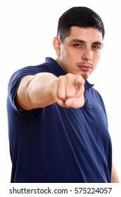 Studio shot of young Hispanic man pointing finger at camera