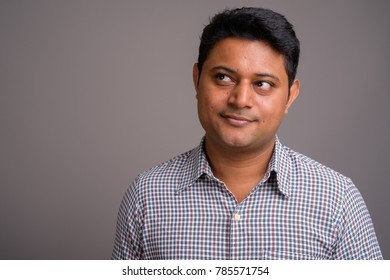 Studio shot of young Indian businessman wearing checkered shirt against gray background