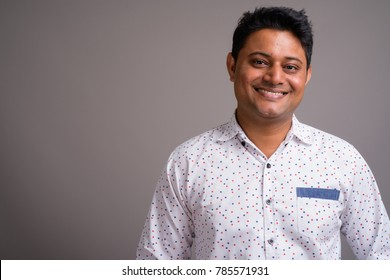 Studio shot of young Indian businessman wearing white shirt against gray background