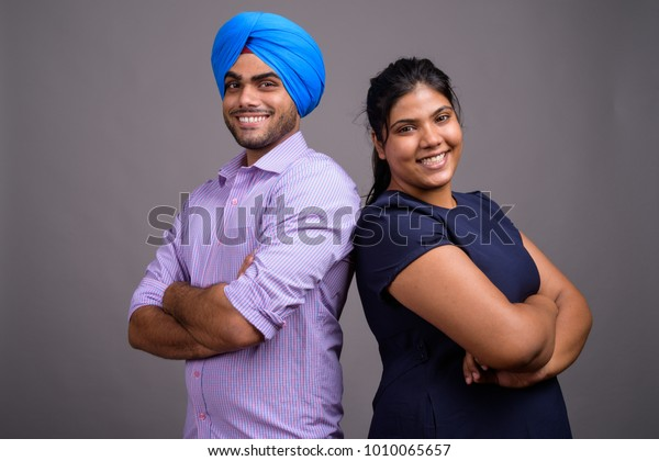 Studio shot of young Indian couple together and in love against gray background