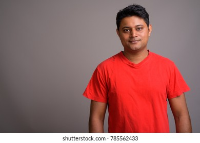 Studio shot of young Indian man wearing red shirt against gray background