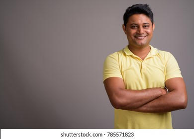 Studio shot of young Indian man wearing yellow polo shirt against gray background