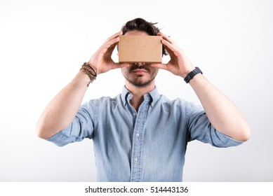 studio shot of a young, male model looking through cardboard virtual reality (VR) headset, isolated on white