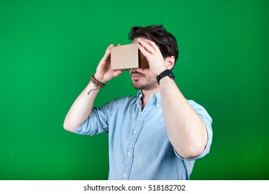 studio shot of a young, male model looking through cardboard virtual reality (VR) headset, isolated on green screen.