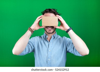 studio shot of a young, male model looking through cardboard virtual reality (VR) headset, and smiling. isolated on green screen.