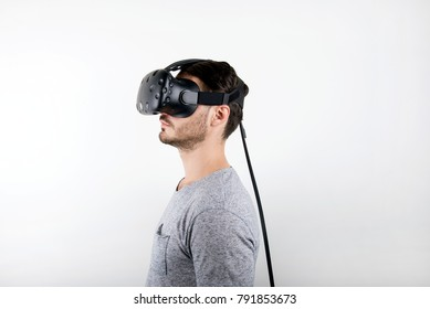 studio shot of a young, male model looking through virtual reality (VR) headset, immersed into his experience. isolated on white background.