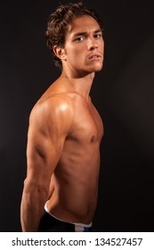 studio shot of a young male with naked torso facing to the side and looking into the camera flexing abdominals and pectoral muscles.