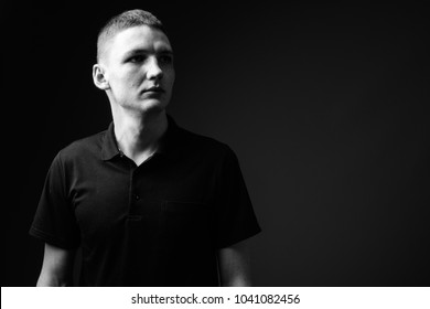 Studio shot of young man against black background in black and white