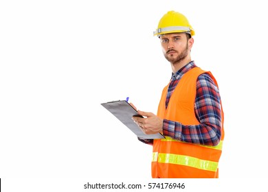 Studio shot of young man construction worker writing on clipboard