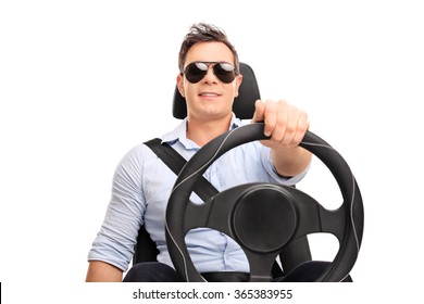 Studio shot of a young man holding a steering wheel and pretending to drive isolated on white background
