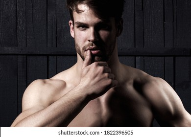 Studio shot of young man looking at the camera. Handsome guy with confident face. Mens sexuality or attraction and charisma