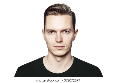 Studio shot of young man looking at the camera. Isolated on white background. Horizontal format, he has a serious face, he is wearing a black T-shirt.