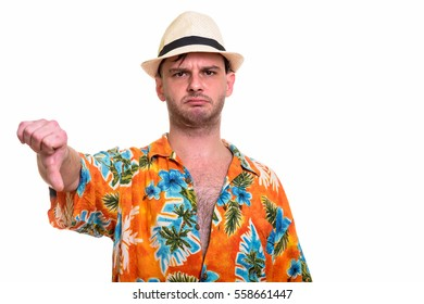 Studio shot of young man looking upset giving thumb down isolated against white background