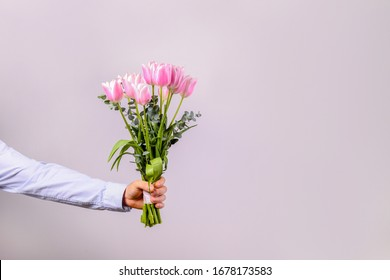 Studio shot of young man wearing cotton shirt, holding beautiful bouquet of pink flowers. Close up, copy space, background.